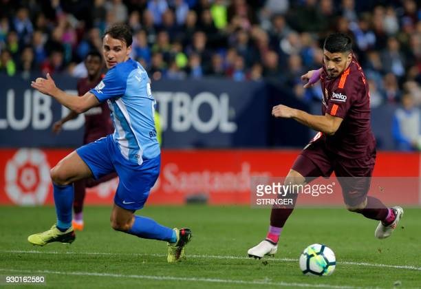 Malaga's Spanish defender Ignasi Miquel vies with Barcelona's Uruguayan forward Luis Suarez during the Spanish league football match between Malaga...