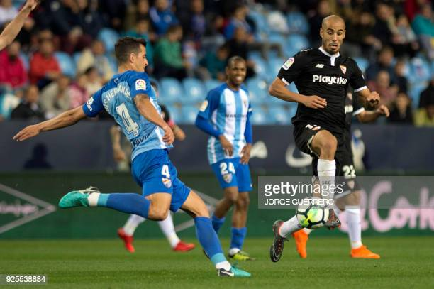 Malaga's Spanish defender Luis Hernandez vies with Sevilla's Argentinian midfielder Guido Pizarro during the Spanish league football match Malaga CF...