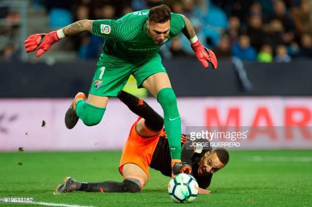 Malaga's Spanish goalkeeper Roberto vies with Valencia's Spanish forward Rodrigo Moreno during the Spanish league football match between Malaga CF...