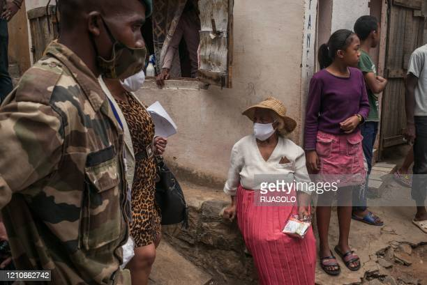 Malagasy army soldiers distribute masks and samples of a local herbal tea touted by President Andry Rajoelina as a powerful remedy against the...