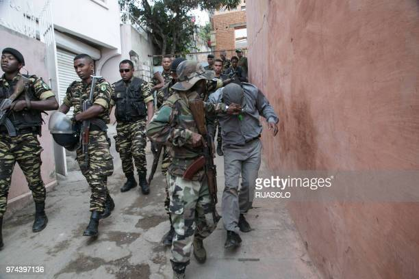 Malagasy police detains a man while escorting hundreds of protestors demonstrating against the new government in the streets of Antananarivo on June...