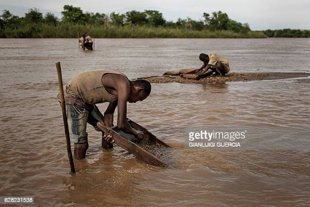 Malagasy workers from an informal Sapphire mine seep soil through a strainer in the waters of a river looking for gems on December 2 2016 on the...
