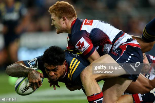 Malakai Fekitoa dives over to score a try while in the tackle of Nic Stirzaker of the Rebels during the round six Super Rugby match between the...