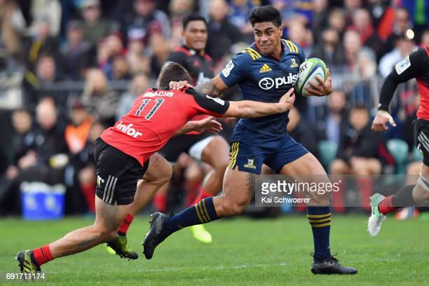 Malakai Fekitoa of the Highlanders is tackled by George Bridge of the Crusaders during the round 15 Super Rugby match between the Crusaders and the...
