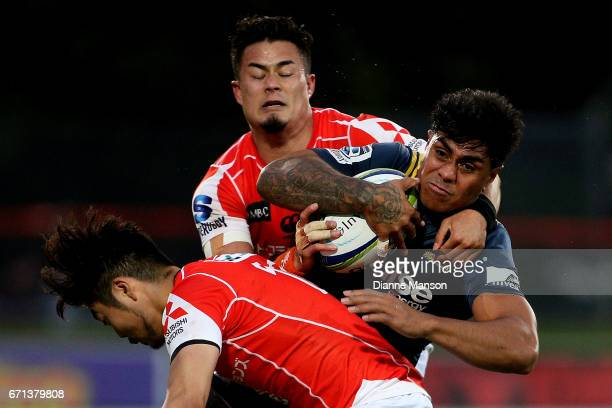 Malakai Fekitoa of the Highlanders tries to break the tackle of Yasutaka Sasakura and Yu Tamura of the Sunwolves during the round nine Super Rugby...