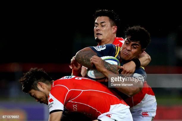 Malakai Fekitoa of the Highlanders tries to break the tackle of Yasutaka Sasakura and Yu Tamura of the Sunwolves during the round nine Super Rugby...