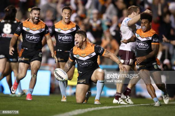 Malakai WateneZelezniak of the Tigers celebrates with his team mates after scoring the winning try during the round 23 NRL match between the Wests...