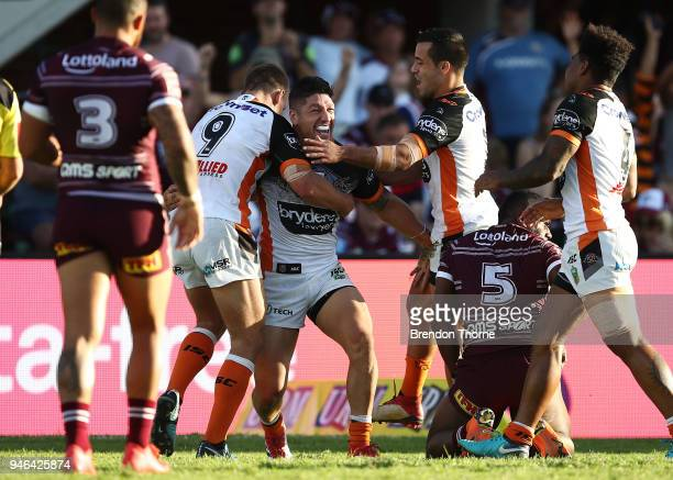 Malakai WateneZelezniak of the Tigers celebrates with team mates after scoring a try during the round six NRL match between the Manly Sea Eagles and...