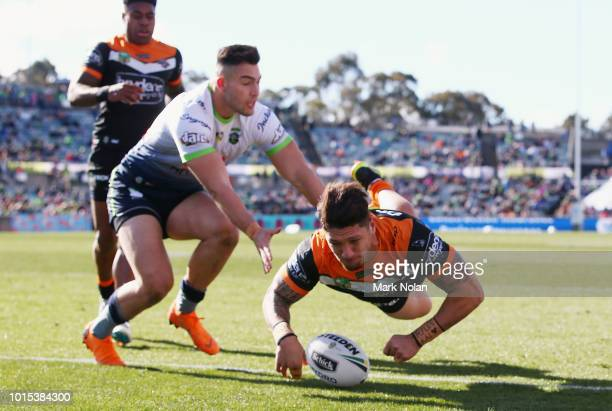 Malakai WateneZelezniak of the Tigers dives to score a try during the round 22 NRL match between the Canberra Raiders and the Wests Tigers at GIO...