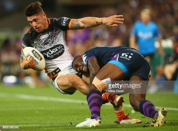 Malakai WateneZelezniak of the Tigers is tackled by Suliasi Vunivalu of the Storm during the round two NRL match between the Melbourne Storm and the...