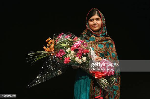 Malala Yousafzai holds a bouquet of flowers, given to her on behalf of the Pakistani Prime Minster during a press conference at the Library of...