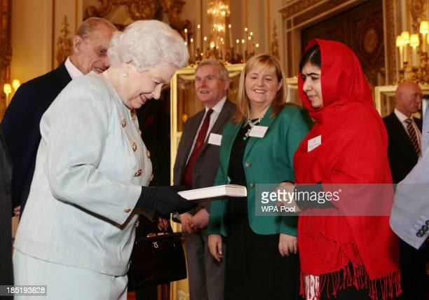 Malala Yousafzai presents a copy of her book to Queen Elizabeth II and Prince Philip, Duke of Edinburgh during a Reception for Youth, Education and...