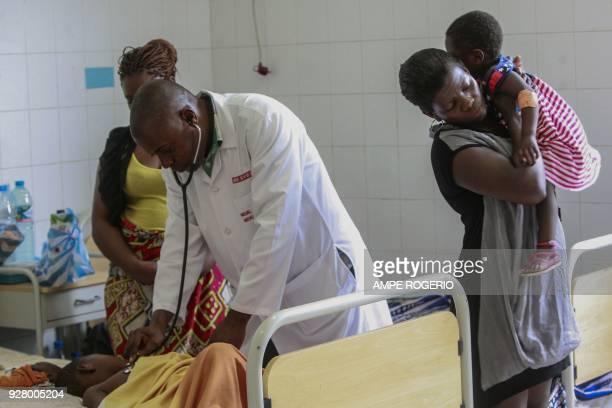 A malaria stricken child is examined by a pediatrician at a hospital in Luanda on February 22 2018 Heavy rains filthy conditions medicine shortages...
