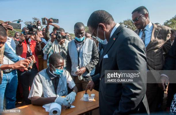 Malawi Congress Party president Lazarus Chakwera dips his index finger in indelible ink before voting during the presidential elections at the...