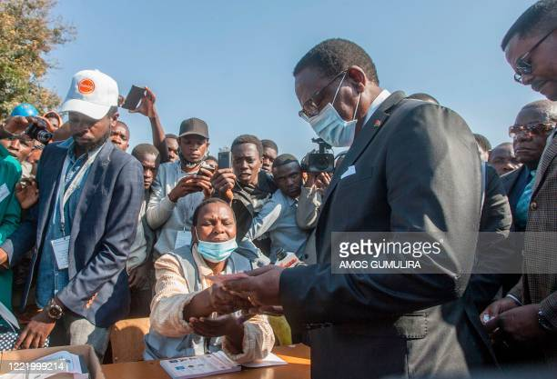 Malawi Congress Party president Lazarus Chakwera receives a ballot paper from an electoral official before voting during the presidential elections...