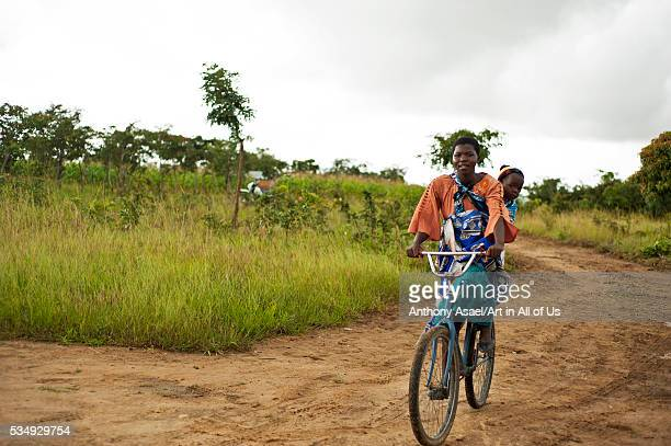 Malawi Mzimba District Tonthowere Community Based Childcare Centres A woman rides a bicycle with her child behind the back as she returns from a...