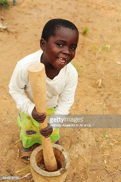 Malawi Mzimba District Tonthowere Community Based Childcare Centres little girl pounding with a mortar