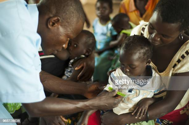 Malawi Northern Region Rumphi Health Surveillance Assistant Bruno Banda checks the breathing rate of 2 year old Grace NKhoma who is diagnosed with...