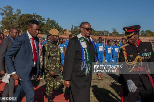 Malawi President Arthur Peter Mutharika wears two football club scarves of the teams of a friendly match as part of national celebrations to...