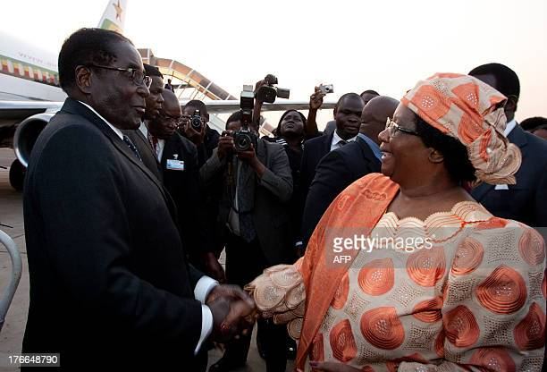 Malawi President Joyce Banda welcomes Zimbabwean President Robert Mugabe at the Kamuzu International Airport in Lilongwe on August 16 ahead of the...