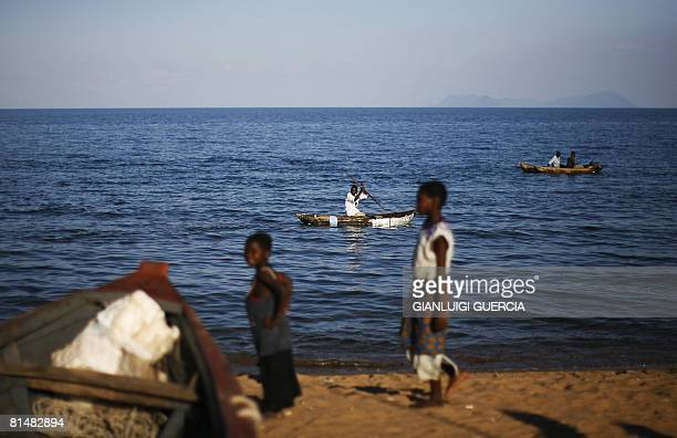Malawian children walk in the sand on May 14 2008 as fishermen paddle on canoes on the shore of Lake Malawi at Senga Bay in Salima district central...