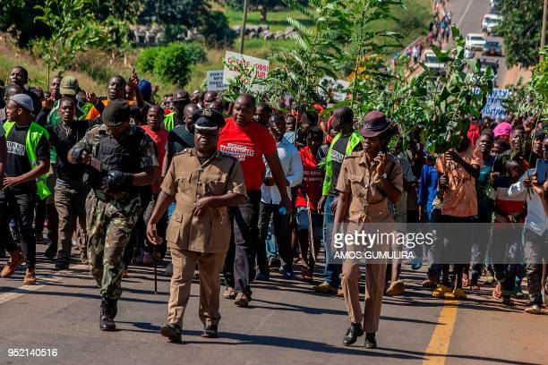Malawian demonstrators march through the streets to protest against alleged poor governance of President Peter Mutharika's government in Lilongwe on...