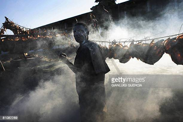 A Malawian fisherman smokes a cigarette on May 14 2008 as he dries freshly caught fish on the shore of Lake Malawi in Salima district central Malawi...