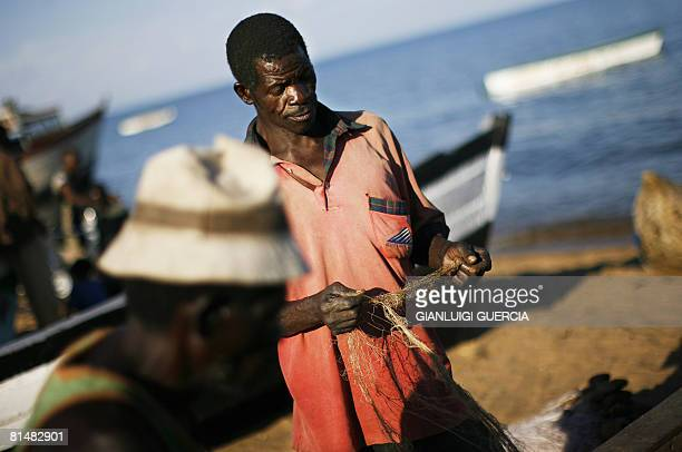 Malawian fisherman stitches his fishing net on May 14 2008 on the shore of Lake Malawi at Senga Bay in Salima district central Malawi Home to more...