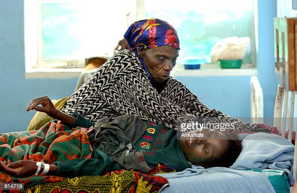 Malawian woman suffering from the HIV virus is helped by a relative in her bed at the Queen Elizabeth Hospital July 4 2002 in Blantyre Malawi In...