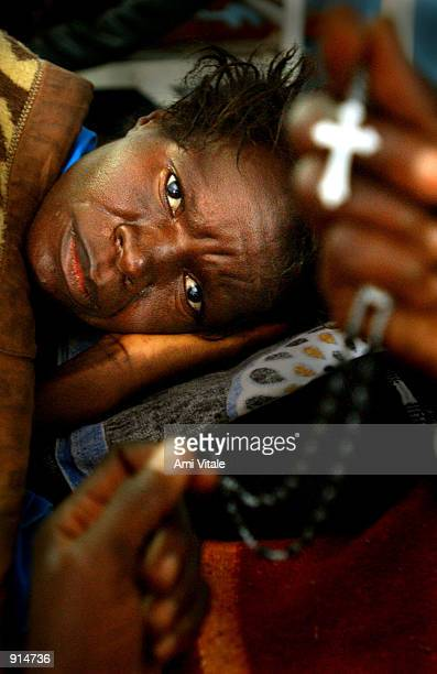 Malawian woman suffering from the HIV virus watches a relative pray for her at the Queen Elizabeth Hospital July 4 2002 in Blantyre Malawi In Malawi...