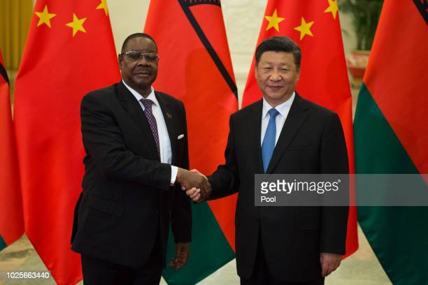 Malawi's President Arthur Peter Mutharika shake hands with China's President Xi Jinping before their bilateral meeting at the Great Hall of the...