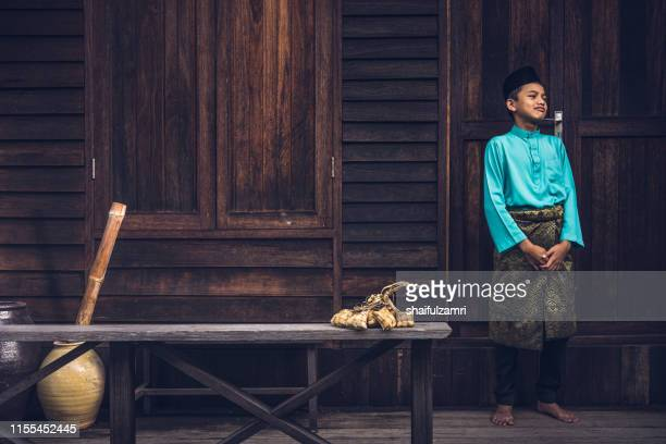 a malay boy in malay traditional cloth showing his happy reaction during hari raya celebration. - shaifulzamri fotografías e imágenes de stock
