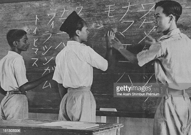 A Malay boy wearing kopiah cap practices Japanese writing on black board in front of a class while his teacher tries to correct his writing in...