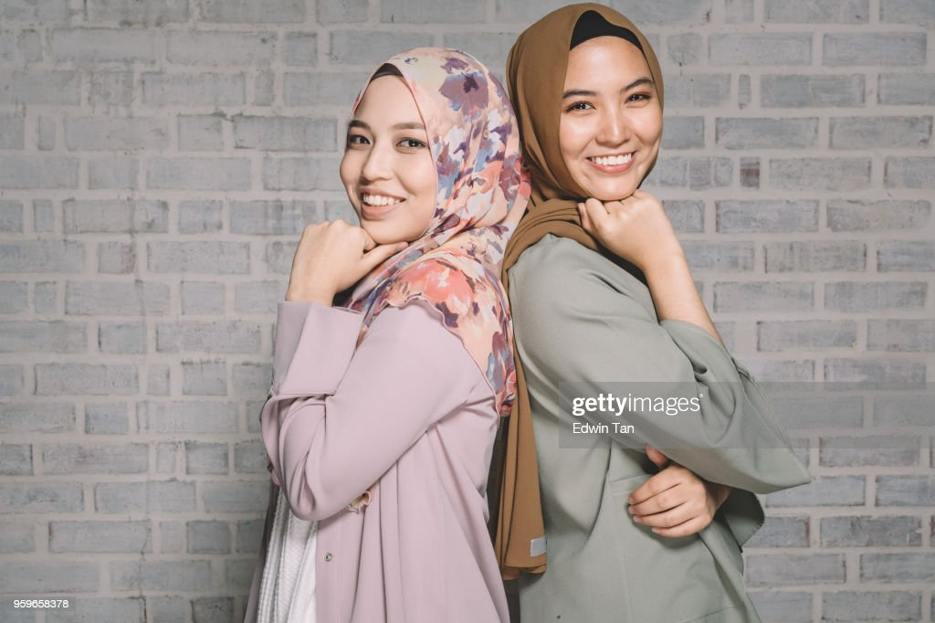 2 malay female back against each other and looking at camera : Stock Photo