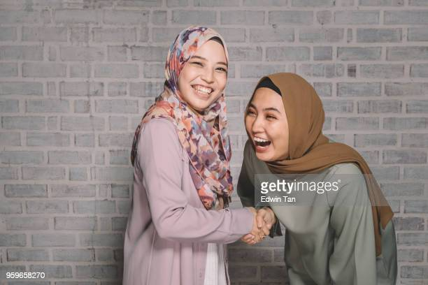 2 malay female greeting to each other and laughing