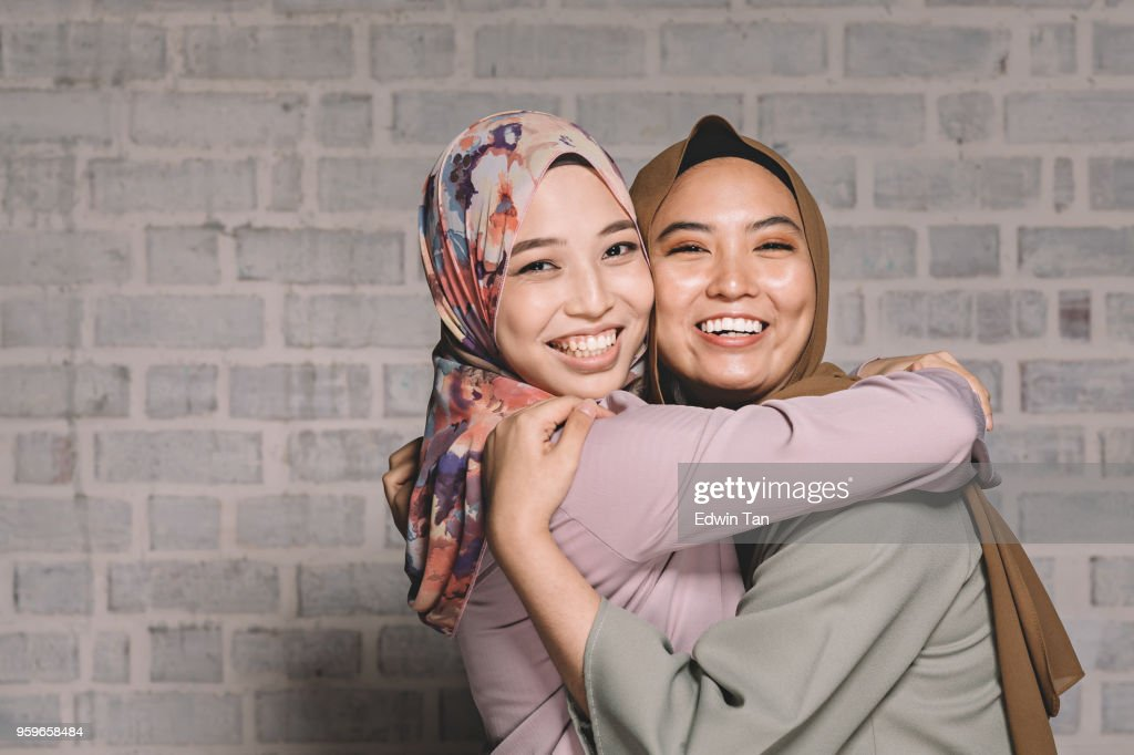 2 malay female hugging and having fun looking at camera : Stock Photo