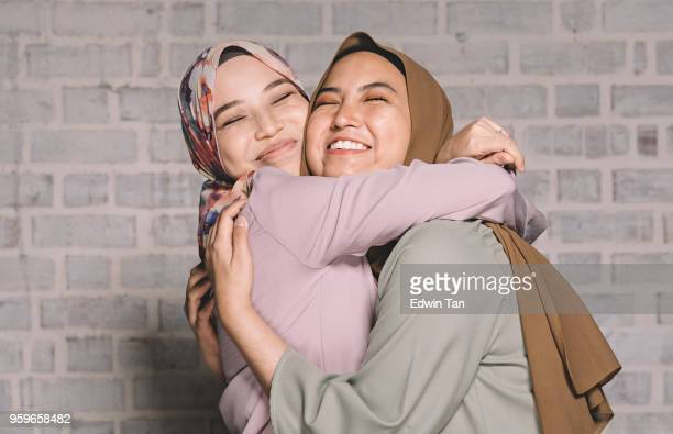 2 malay female hugging and having fun