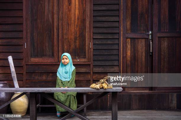 a malay girl in malay traditional cloth showing his happy reaction during hari raya celebration. - shaifulzamri stock-fotos und bilder