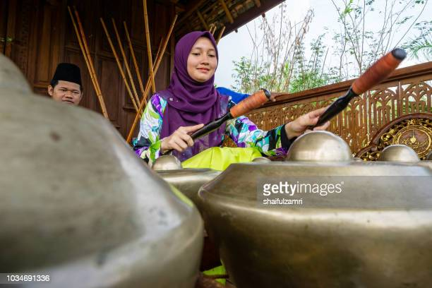 "malay girl playing a traditional musical instrument namely ""cak lempong"" - a small kettle gong which gives its name to an ensemble of four or five talempong, which is present in the different configurations of the nobat. - shaifulzamri stock pictures, royalty-free photos & images"