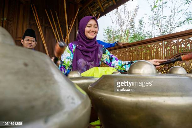 Malay girl playing a traditional musical instrument namely 'Cak Lempong' - a small kettle gong which gives its name to an ensemble of four or five talempong, which is present in the different configurations of the Nobat.