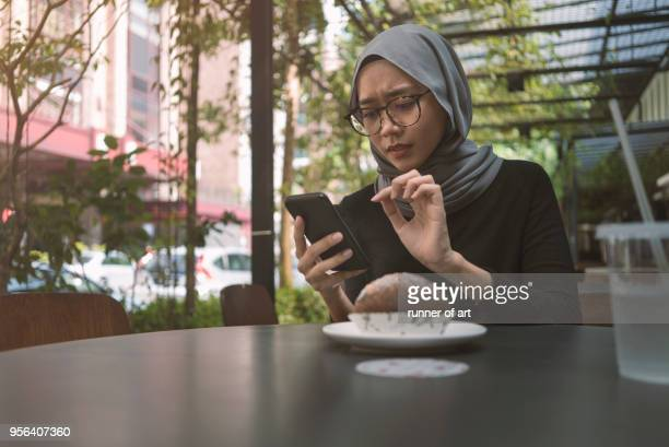 malay girl with hijab with her smartphone - religious dress stock photos and pictures