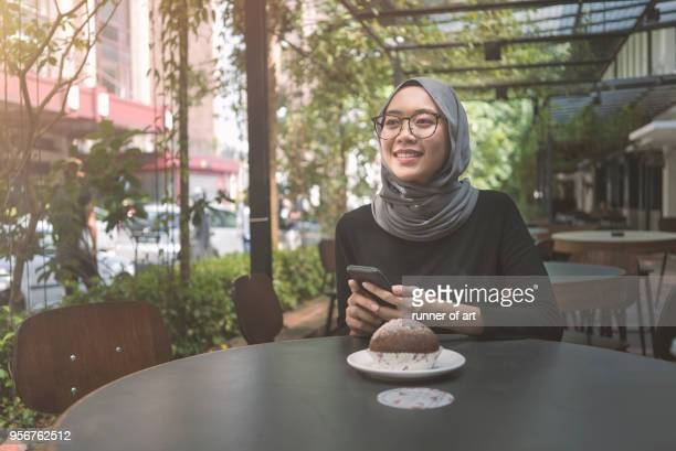 malay girl with hijab with her smartphone - malaysia beautiful girl stock photos and pictures