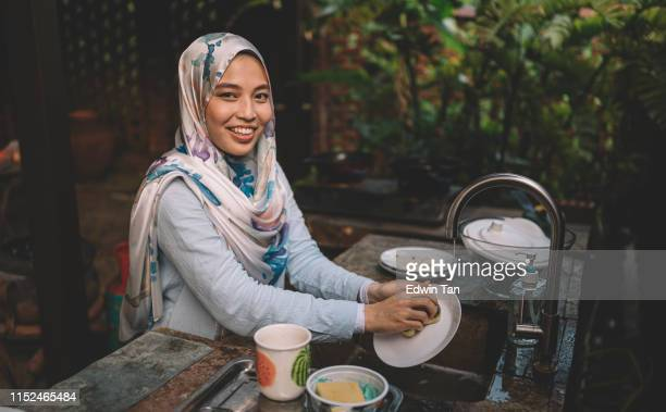 a malay lady cleaning and washing dishes after dinner party looking at camera - cleaning after party stock pictures, royalty-free photos & images