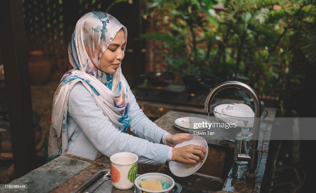 A Malay lady cleaning and washing dishes after dinner party : Stock Photo