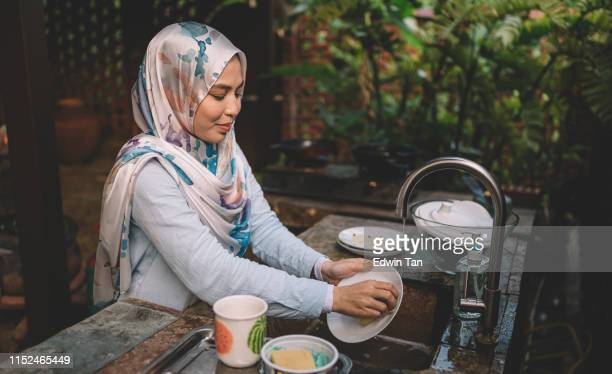 a malay lady cleaning and washing dishes after dinner party - cleaning after party stock pictures, royalty-free photos & images