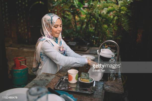 a malay lady cleaning and washing dishes after dinner party - messy house after party stock pictures, royalty-free photos & images