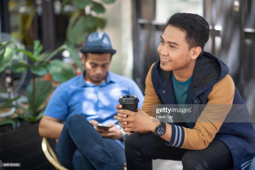 2 malaiischen Rüden sitzen am Straßenrand und bonding Zeit miteinander zu reden : Stock-Foto