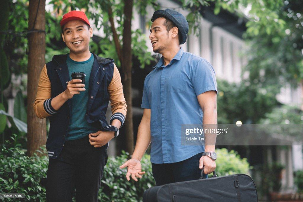 2 malaiischen Rüden Hut trägt, sprechen und gehen auf der Straße : Stock-Foto