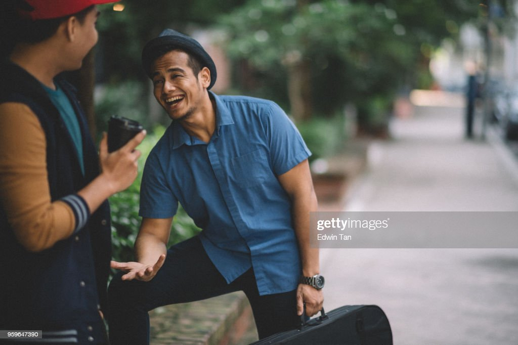 2 malay males wearing hat,  talking and walking on the street : Stock Photo