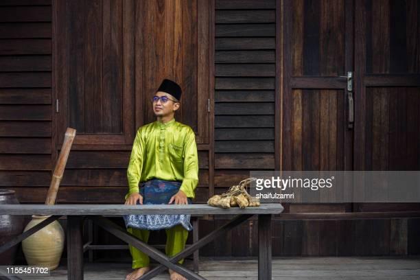 a malay man in malay traditional cloth showing his happy reaction during hari raya celebration. - shaifulzamri stock-fotos und bilder